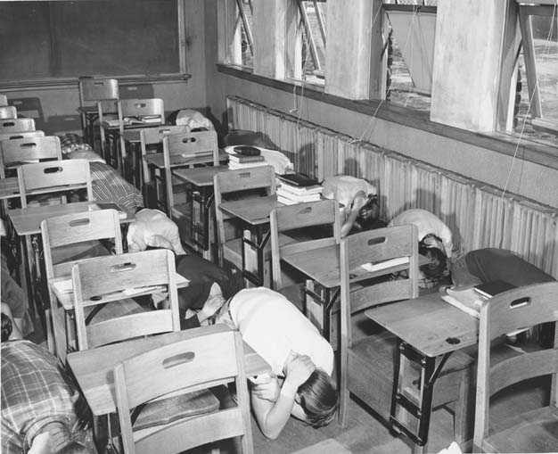Black and white photograph of an atomic attack drill taken in a California classroom on March 15, 1951. The photograph shows two rows of six students kneeling on the floor next to their desks in a tucked position.