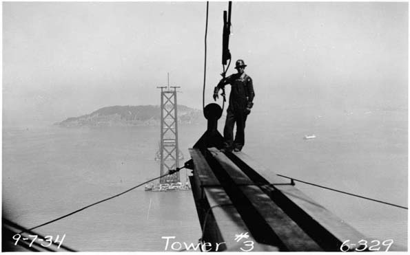 This black and white photograph of the construction of the San Francisco-Oakland Bay Bridge was taken on September 7, 1934 and shows a bridge worker standing on a steel beam suspended high above the water.