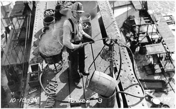 This black and white photograph of the construction of the San Francisco-Oakland Bay Bridge was taken on October 18, 1934. The image shows a male bridge worker standing on a platform driving rivets into the steel.