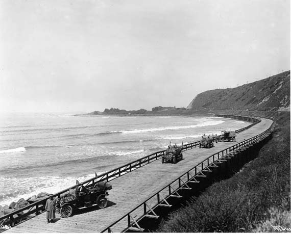 This black and white photograph of the Rincon Causeway in Ventura County was taken in 1912. The photo shows four automobiles on the wooden causeway that runs along the beach in Ventura County.
