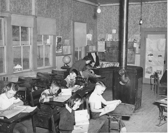 This photograph of a small classroom in San Benito County was taken between March and April of 1949. The image shows several children reading at their desks while their teacher assists a student with his studies.