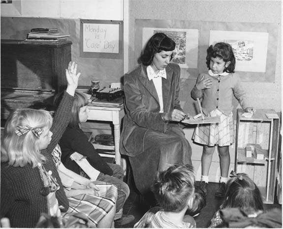 Black and white photograph taken at a UCLA elementary school classroom in January 1950. The photograph shows several children seated around their teacher who is showing them a student's project.