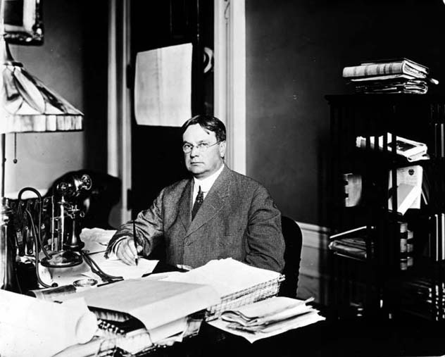 Black and white photograph of Governor Hiram Johnson taken around the year 1912. The image shows Governor Hiram Johnson seated at a desk and writing with a pen.