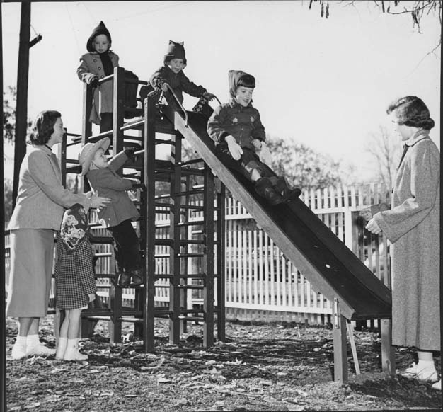 This photograph of children playing on a slide in a playground was taken in January 1950 at Fresno State College. Two women assist the five children as they climb up and slide down the slide.