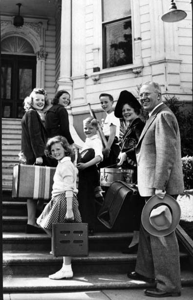 This black and white photograph of Governor Earl Warren with his wife and five children was taken around the year 1943. The image shows the Warren family carrying their luggage and standing on the front steps of the California Governor's Mansion.