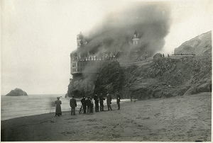 Black and white photograph showing smoke billowing from the restaurant called the Cliff House, located in San Francisco. On the beach stands a group of onlookers.