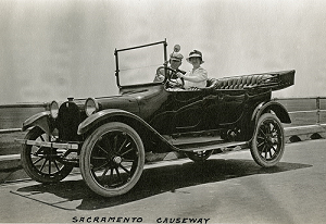 Black and white photograph of William and Grace McCarthy in their automobile crossing the Sacramento Causeway in about 1916.