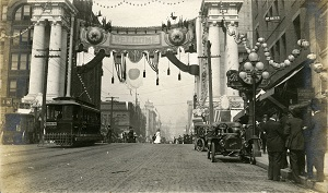 96-07-08-alb08-136, Seattle street scene dominated by a banner welcoming fairgoers to the Alaska-Yukon-Pacific Exposition, celebrating the development of the Pacific Northwest, 1909
