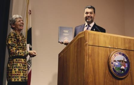 Photograph of former Legislative Analyst Elizabeth Hill and Secretary of State Alex Padilla. Ms. Hill is on the right, the Secretary is to the left and standing at a podium. Secretary Padilla has a bound copy of Ms. Hill's oral history in his hand.