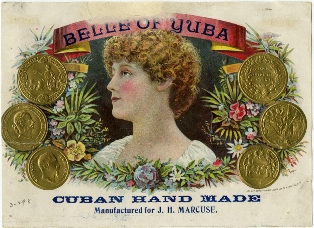 Image of a beautiful young woman with reddish wavy hair, alabaster skin, and rosy cheeks. She is framed by a red ribbon at the top that reads Belle of Yuba; there are gold coins continuing the frame on the left and right; and at the bottom are the words Cuban Hand Made, Manufactured by J.H. Marcuse