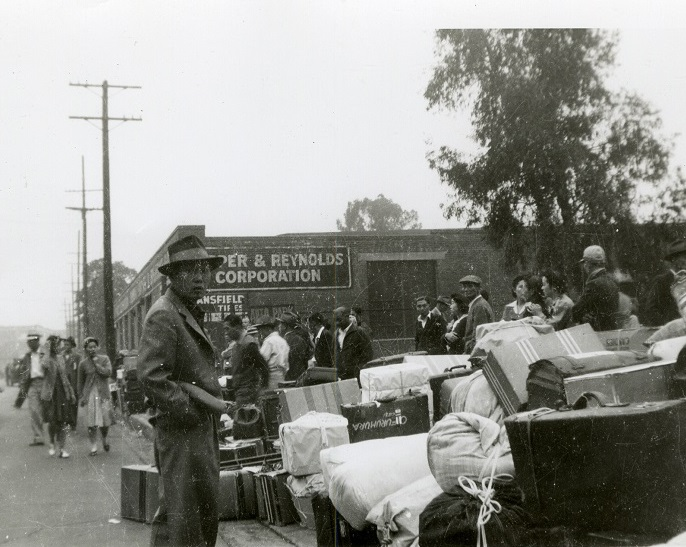 Black and white photo showing a number of Japanese-Americans standing amidst bundled of belongings, awaiting to be transported to incarceration camps