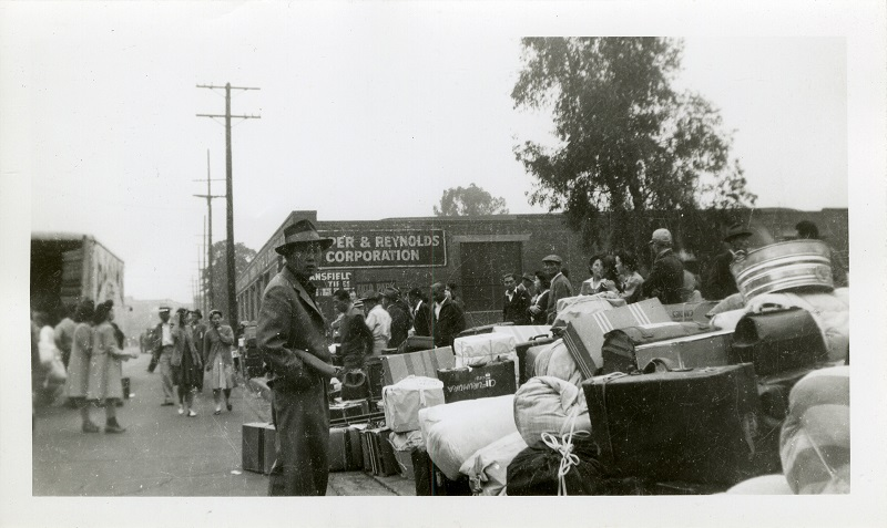 Black and white photo showing a number of Japanese-Americans standing amidst bundles  of belongings, awaiting to be transported to incarceration camps