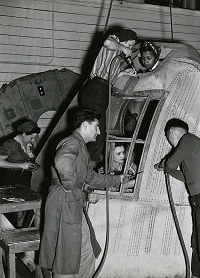 Black and white photograph showing four women and two men riveting the nose of an airplane.